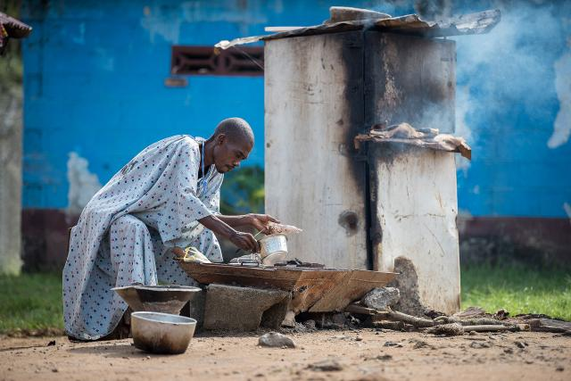 A male patient at the Ganta United Methodist Hospital prepares a meal. The hospital provides kitchen facilities for patients who wish to cook for themselves during their stay.